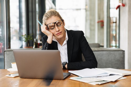 Tired business woman sitting at her computer, in need of a sleep coach.