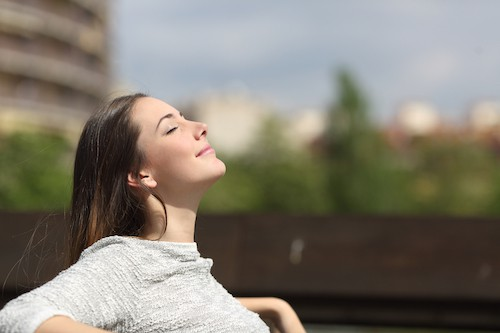 Photo of woman basking in the sun as a way to cope with parent sleep deprivation
