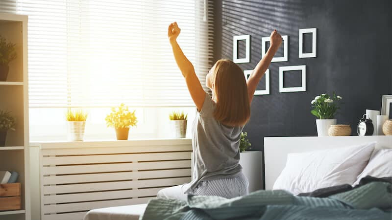 Image of woman stretching in bed, refreshed after working with an adult sleep coach