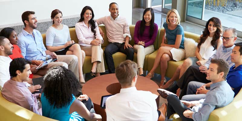 Image showing employees sitting in a circle. They're well rested after working with a sleep coach.