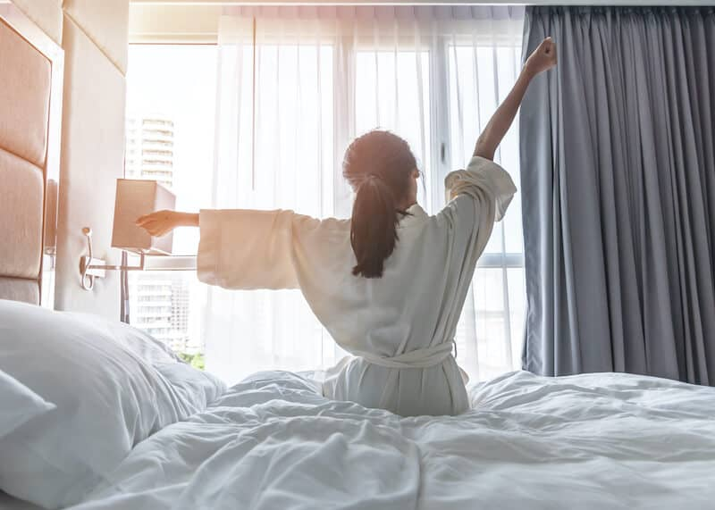 Image of woman waking up refreshed after working with a sleep coach for adults