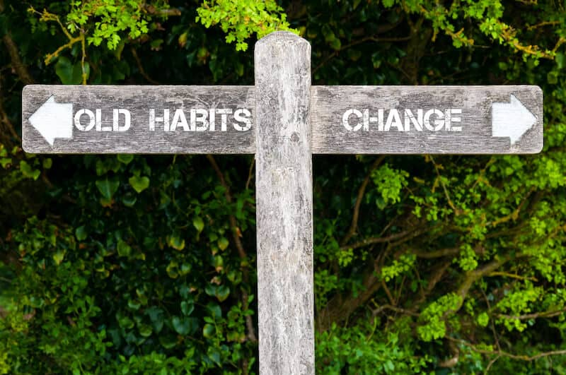 Photo of sign pointing one way to old habits, and the other way to change. Indicates that the cost of sleep coach services is worth it for change.