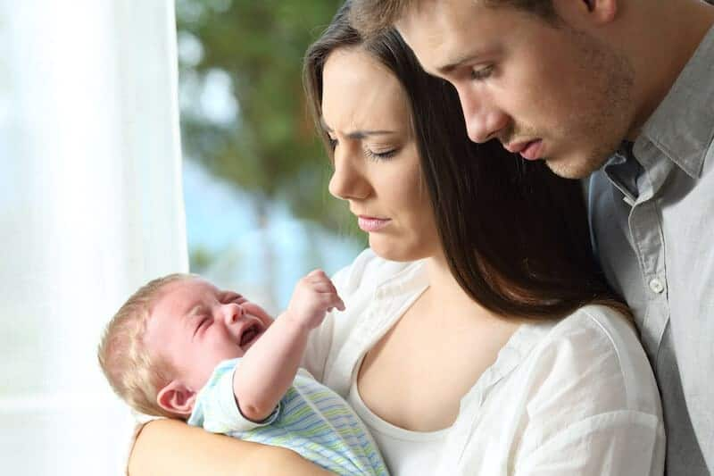 Image of concerned parents looking at baby and needing help from a sleep coach for babies and toddlers.