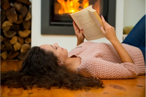 Photo of woman reading as a way to relax while dealing with parent sleep deprivation